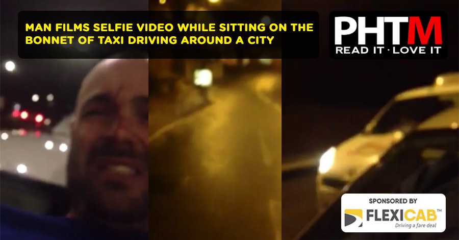 MAN FILMS SELFIE VIDEO WHILE SITTING ON THE BONNET OF TAXI DRIVING AROUND A CITY